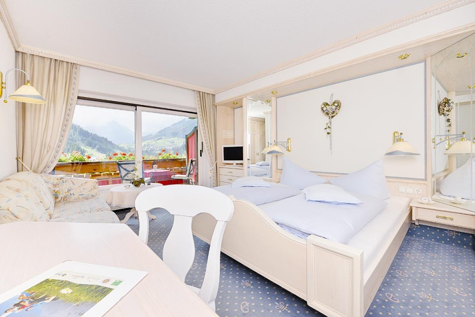 Schlafbereich und gemütlicher Wohnbereich im Doppelzimmer Enzian